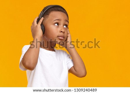Music, relaxation, fun, joy and modern electronic gadgets concept. Adorable dark skinned black male kid enjoying favorite tracks or listening to radio via wireless headphones, looking upwards