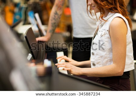 music, sale, people, musical instruments and entertainment concept - close happy man and woman playing piano at music store