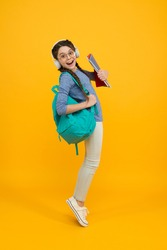 Music school. Happy girl back to school. Schoolchild carry backpack yellow background. School and education. Knowledge day. September 1. Startup. First day of school. Always learning.