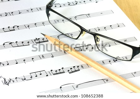 music sheet with pencil and glasses