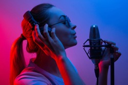 music, show business, people and the voice of a singer or DJ with headphones with glasses and a microphone singing a song in the recording studio. Discoteka, party, light-music, party, party, party