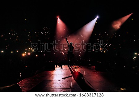 Music show. Guitarist in front of crowd on scene in night club. Bright stage lighting, crowded dance floor. Phone lights at concert. Band red silhouette crowd. People with cell phone