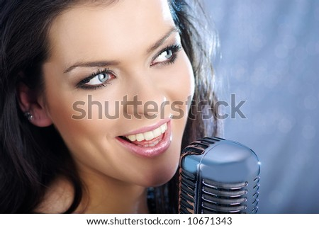 Music star.Sexy woman singing in retro mic