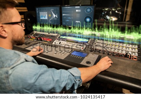 music, technology and equipment concept - man at mixing console with computer monitors in sound recording studio #1024135417