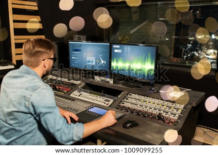 music, technology, people and equipment concept - man at mixing console in sound recording studio over lights