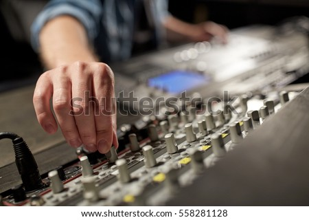 music, technology, people and equipment concept - man using mixing console in sound recording studio #558281128