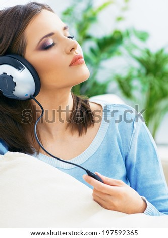 Music woman. Girl listening music with headphones. Home portrait.