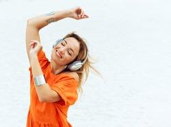 Music - woman wearing headphones listening to music. Relaxing beautiful young Caucasian woman is enjoying music and dancing on a beach.