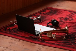 Musical attributes.Laptop headphones sheet music with a pencil two wind musical instruments on a wooden floor with a red blanket.Set of the musician of the creative person.Work and leisure concept