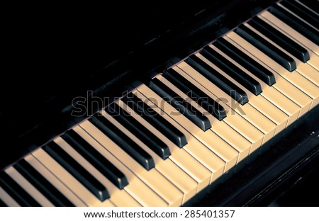 Musical background with piano keys. Music concept with old classic musical jazz instrument. Piano keys in retro style with copy-space for text on black color background.