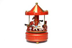 Musical carousel with horses. Red, white horses go round. Toy. Vintage carousel isolated on white background. Closeup. Front view.