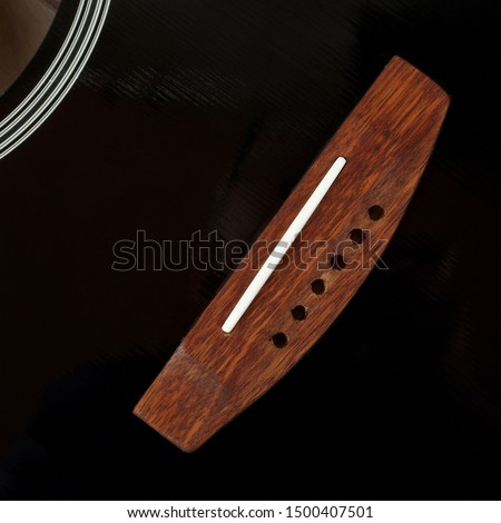 Musical instrument - Fragment top view bridge vintage acoustic guitar without strings.