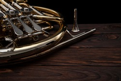 Musical instrument, French horn on a wooden surface on a black background