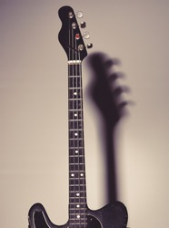 Musical instrument with four strings for playing metal or jazz music. Music and hard rock concept. Guitar in deep black color on black background with shadow. Electric guitar stands on dark chair.
