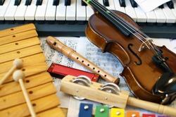 Musical instruments for children: xylophone, children's violin, tambourine, flute, harmonica, piano keyboard.