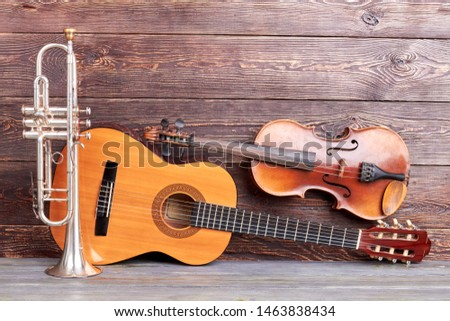 Musical instruments of vintage style. Trumpet, acoustic guitar and violin on wooden background. Classical musical instruments. #1463838434