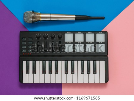 Musical mini mixer and microphone on a background of three colors. Equipment for the music Studio. The view from the top.