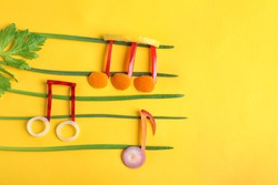 Musical notes made of vegetables and fruits on color background, top view. Space for text
