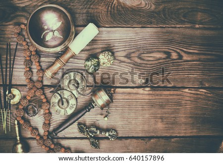 Musical religious instruments for Buddhist practices and meditations, brown wood background, empty space on the right, vintage toning #640157896