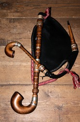 Musical traditional instrument bagpipes on wooden background.