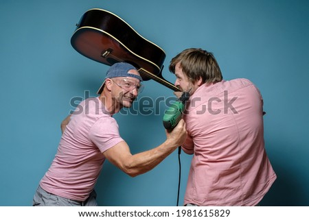 Musician and construction worker, they started a fight over the noise, one threatens with a drill, the other with a guitar. ストックフォト ©