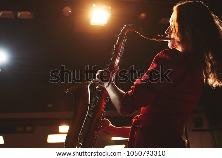 Musician girl in a red dress with a saxophone on stage #1050793310