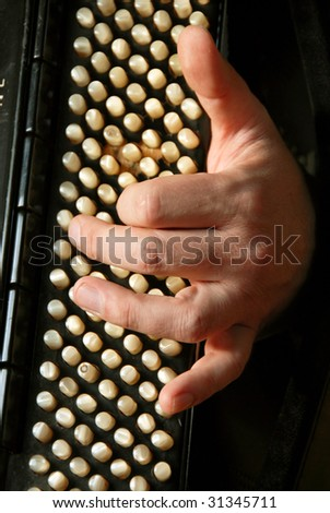 musician hand playing accordion closeup in dramatic shadows