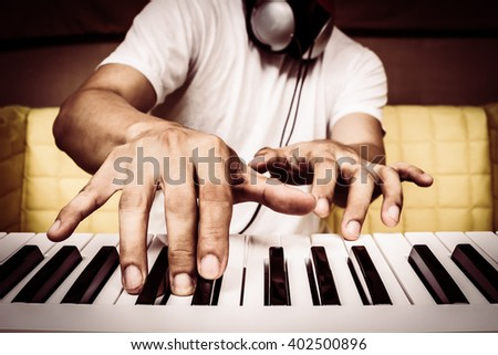 musician hands playing white piano on yellow seat + art filter for music background