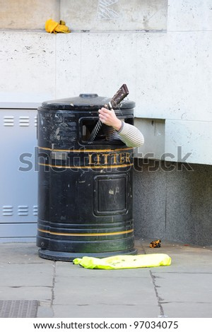 Musician inside a trash bin plays guitar.