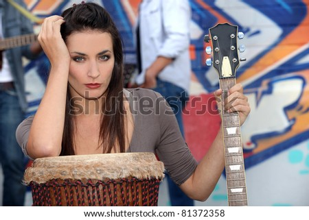 Musician leaning on a drum and holding a guitar - stock photo