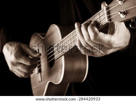 musician playing a hawaiian ukulele,sepia image