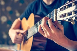 musician playing acoustic guitar, live music background