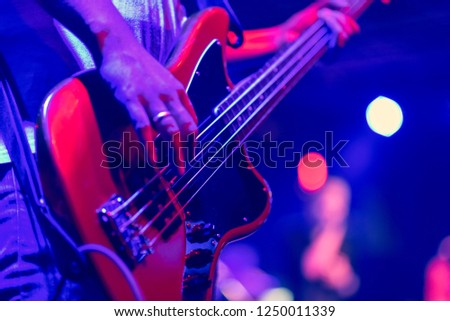 musician playing bass guitar on stage