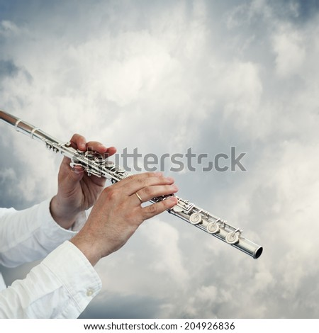 musician playing flute on a neutral background