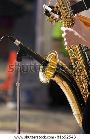 Musician playing jazz saxophone during live performance on stage