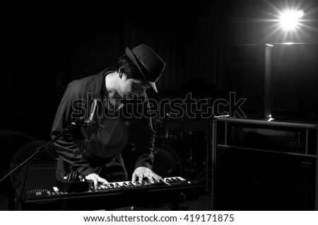 Musician playing keyboard with music instrument and lens flare from spot light on dark background, Musician concept