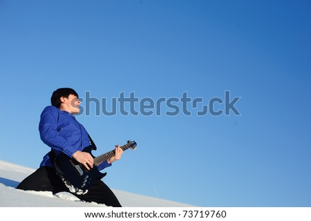 Musician playing on electro guitar in the snowdrift