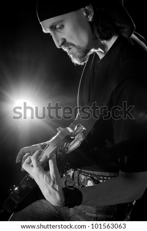 musician playing on his electric guitar
