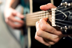 musician playing on the acoustic guitar