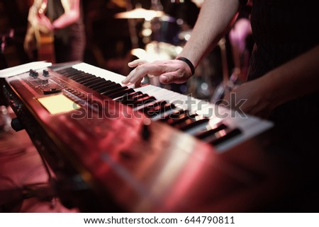 Musician playing on the keyboard synthesizer piano keys. Musician plays a musical instrument on the concert stage - Shutterstock ID 644790811