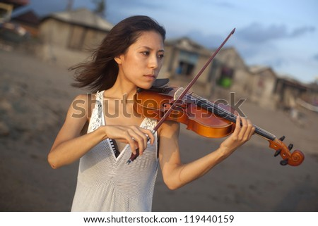 Musician playing on violin at coast Bali