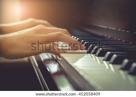 Musician playing piano in church with vintage filter.
