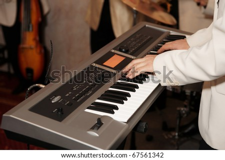 Musician playing synthesizer, band in background, TMs removed