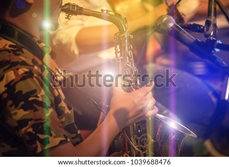 musician playing the saxophone on band in nigh concert #1039688476