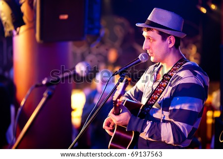 musician plays a guitar at a concert