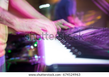 Musician plays keyboards in a rock band #674524963
