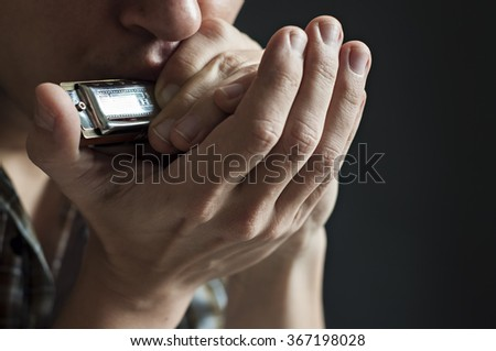 Musician plays the harmonica on black background - Shutterstock ID 367198028
