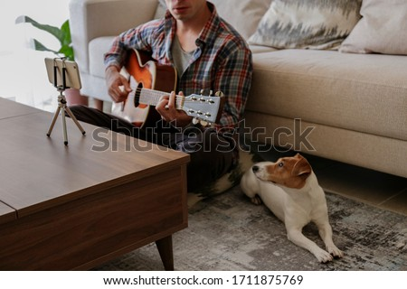 Musician practicing acoustic guitar exercises, taking online musical courses, reading notes from phone on tripod & a pet friend listening his music. Jack Russell Terrier puppy. Background, close up.