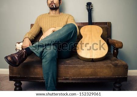 musician sitting on old sofa...