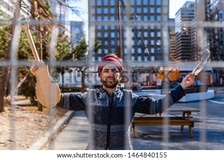 Musician stands behind city park fence. A young Caucasian man is seen standing behind a chain link fence in an urban plaza with skyscrapers, holding an eagle feather and acoustic instrument. #1464840155
